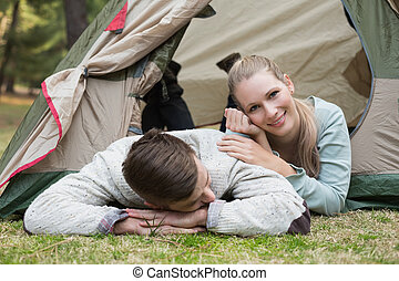 Young couple camping in the wilderness - Happy couple lying...