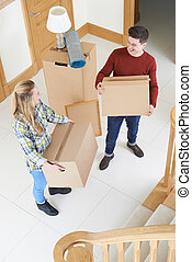 Young Couple Carrying Boxes On Moving In Day