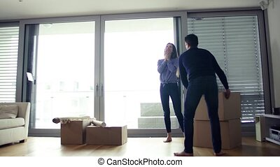 Young couple carrying cardboard boxes, moving in a new home.