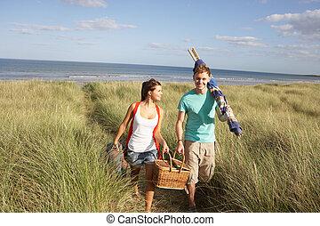 Young Couple Carrying Picnic Basket And Windbreak Walking...