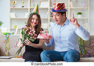 Young couple celebrating birthday with cake