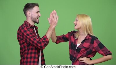 Young couple celebrating with high-five together