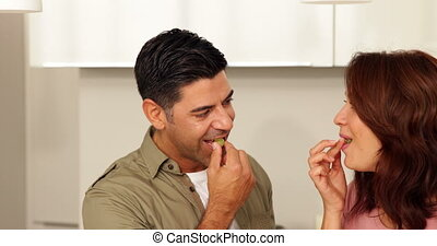 Young couple chatting and eating grapes