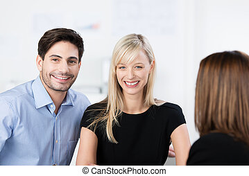 Young couple chatting to a friend or adviser - Attractive...
