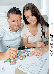 young couple checking architecture plans