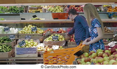 Young couple choose fresh fruits in a large supermarket. Man selecting fresh ananas in grocery store supermarket sale, shopping marketplace food with grocery
