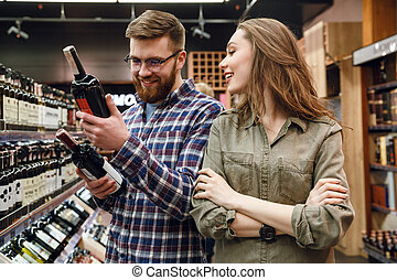Young couple choosing bottle of wine