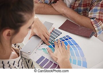 Young couple choosing new colors for the house