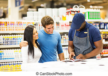 young couple choosing paint color with help of hardware store wo