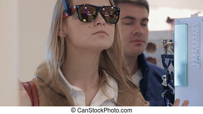Young couple choosing sunglasses in the store