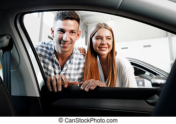Young couple choosing their new car in a car shop