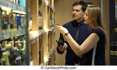 Young couple choosing wine in the shop