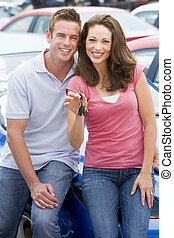 Young couple collecting new car