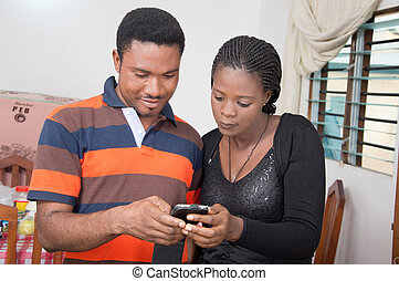 young couple consulting a phone. - This gentleman shows to...