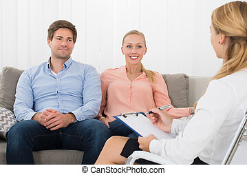 Young Couple Consulting With Psychologist - Happy Young...