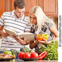 Young Couple Cooking - Young couple look at a recipe book in...