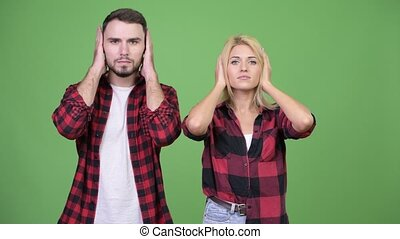 Young couple covering ears together as three wise monkeys...