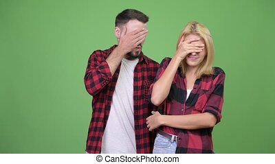 Young couple covering eyes together not wanting to see...