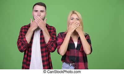 Young couple covering mouth together as three wise monkeys...