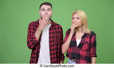 Young couple covering mouth together while looking guilty -...
