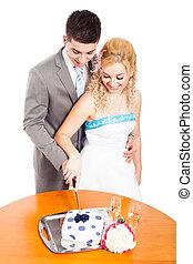 Young couple cutting wedding cake