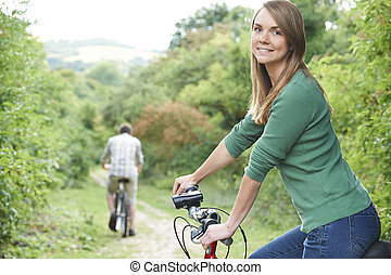 Young Couple Cycling Along Country Track