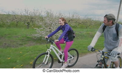 Young couple cycling happily together through a sunny park on street