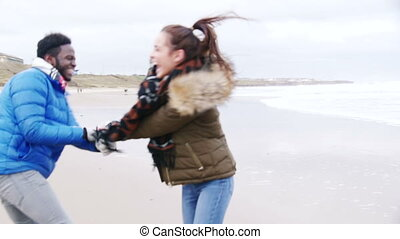 Young Couple Dance On A Winter Beach - A young couple laugh...