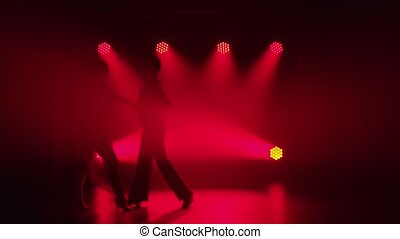 Young couple dancing ballroom dance elements. Rumba, salsa, tango, flamenco. Silhouette of dance partners man and woman dance passionately in the dark against the backdrop of red spotlights. Slow motion.