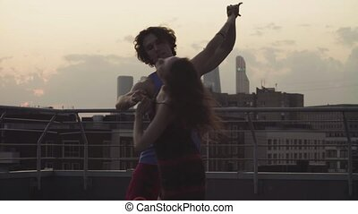 Young couple dancing on sunset