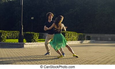 Young couple dancing on the square