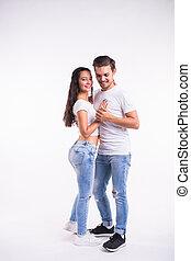 Young couple dancing social dance bachata, merengue, salsa, kizomba. Two elegance pose on white room