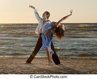 young couple dancing tango on the beach