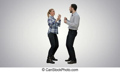 Young couple dancing together on white background.