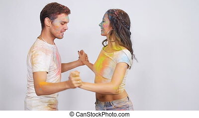 Young couple dancing with holi paints on a white background....