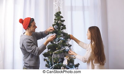 Young couple decorates a Christmas tree.
