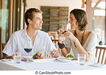 Young Couple Dining - A young couple sitting at a table at...