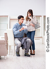 Young couple disappointed with price in furniture store