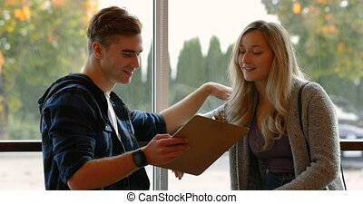 Young couple discussing over a clipboard in cafe 4k
