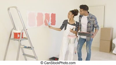 Young couple discussing shades of paint color together as...