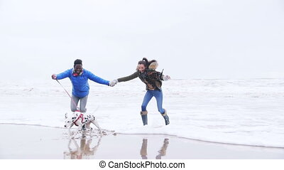 Young Couple Dodge Waves On Winter Beach - A young couple...