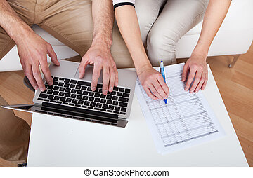 Young couple doing finances at laptop