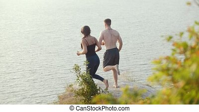 Young couple doing morning exercises on rocky cliff by the river