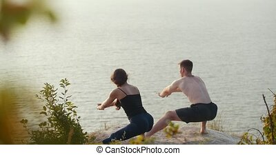 Young couple doing morning warm-up on the cliff by the...