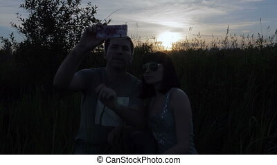 Young couple doing selfie, photo on their phone in the field at sunset.
