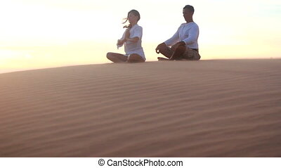 Young couple doing yoga exercises on a desert at sunrise or sunset