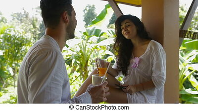 Young Couple Drink Juice Talking On Balcony In Hotel, Happy...
