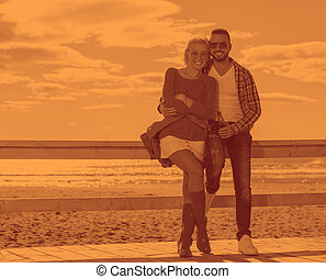young couple drinking beer together at the beach