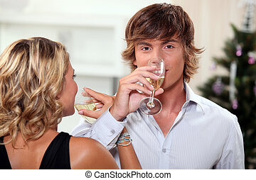 Young couple drinking champagne at Christmas
