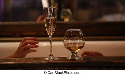 young couple drinking foaming champagne and cognac in old bathroom close up